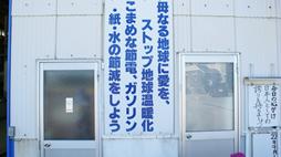 看板「母なる地球に愛を、ストップ地球温暖化 こまめな節電、ガソリン・紙・水の節減をしよう」